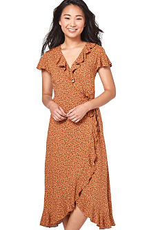 A young woman wearing a brown short sleeved dress. Shop dresses.