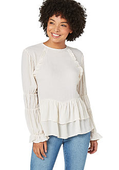 A young woman wearing a white long sleeved top & blue jeans. Shop tops.