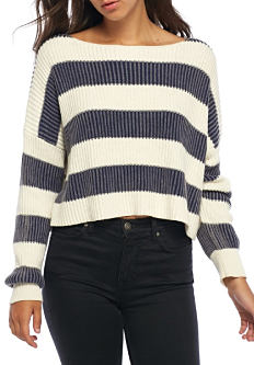 A young woman wearing a white & gray horizontal striped sweater & black jeans. Shop sweaters.
