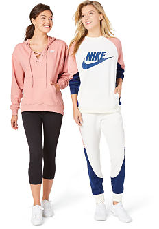 A young woman wearing a peach hoodie, black pants & white sneakers standing next to a young woman wearing a white, blue & peach Nike logo jersey, white & blue pants & white sneakers. Shop activewear.