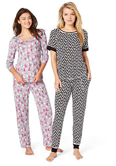 A young woman wearing gray, red & white patterned print pajamas standing next to a young woman wearing a black & white pajamas. Shop pajamas & loungewear.