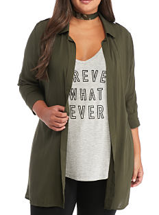 A woman a green jacket over a gray graphic tee. Shop tops.