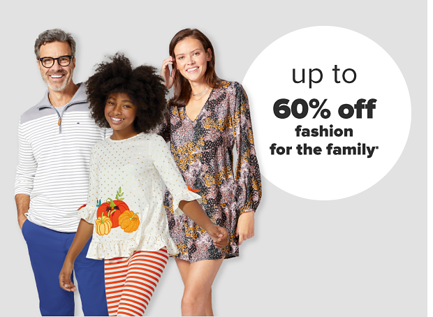 A man in a gray and white striped pullover and blue pants. A woman in a gray, orange and pink long sleeve mini dress. A girl in a long sleeve shirt with a pumpkin decal and ruffles along the edges with orange and white striped leggings. Up to 60% off fashion for the family.