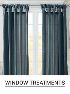 A window with gray floor length curtains. Shop window treatments.