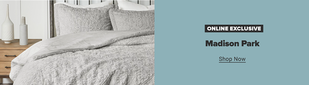 A full bed with a light gray bedding set accented with tones of blue. Two silver nightstands. A small bench. Online exclusive. Madison Park. Shop now.