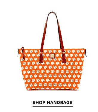 A orange and white Clemson Tigers logo print handbag with brown leather straps. Shop handbags