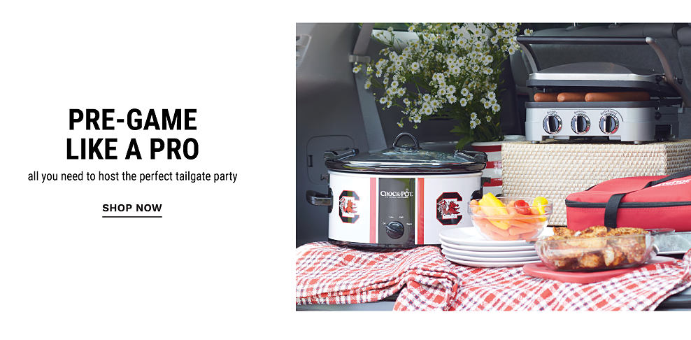 A tailgate spread with a red, black and white tablecloth, a black, red and white University of South Carolina Gamecocks ogo crockpot, a portable grill cooking hot dogs, a stack of white plates and a red and black picnic bag. Pre Game Like a Pro. All you need to host the perfect tailgate party. Shop now