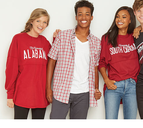 A young woman wearing a red and white Alabama Crimson Tide sweatshirt and blue jeans, a young man wearing a red and white plaid short sleeved button front shirt, a white T shirt and blue jeans, a young woman wearing a red and white University of South Carolina Gamecocks sweatshirt and blue jeans and a young man wearing a navy red and white University of South Carolina Gamecocks sweatshirt and blue jeans. Team Apparel. Shop women.