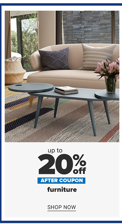 A beige couch with a navy throw pillow and a beige stripe throw pillow. A light gray coffee table and an area rug with color block stripes in a variety of colors. Up to 20% off, after coupon, furniture. Shop now.