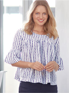 A woman wearing a navy and white striped top and blue pants. Shop tops.