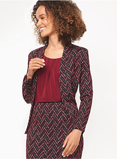 A woman wearing a burgundy top & a red & blue patterned jacket & skirt. Shop suits.