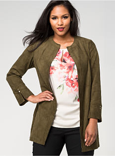 A woman wearing a green-brown jacket, black pants, black shoes & a white top with a floral print. Shop jackets.