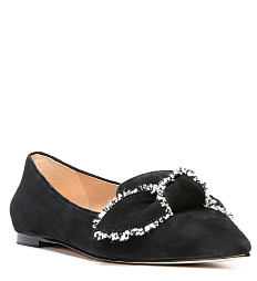 A black suede flat with white bow detail. Shop flats.