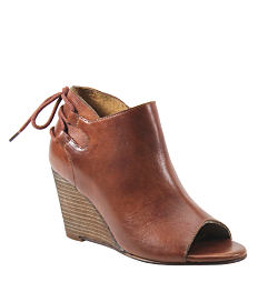 A brown leather chunky-heeled shoe with lace strap detail. Shop designer.
