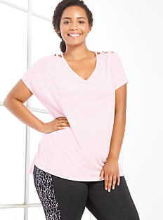 A woman wearing a light pink tee & black workout pants. Shop activewear.