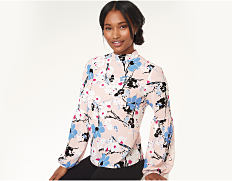 A woman wearing a multi-colored print blouse & black pants. Shop tops.