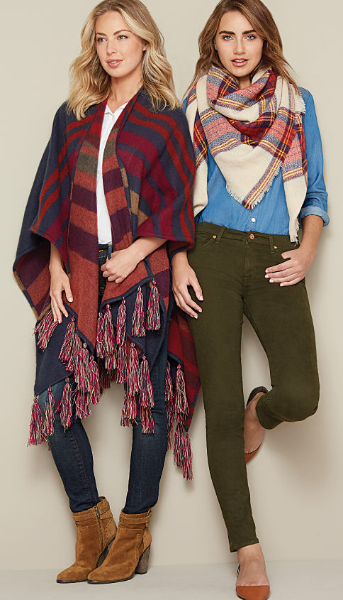 A woman wearing a multi-colored print poncho, jeans & brown suede boots standing next to a woman wearing a plaid oversized scarf, a blue button-front shirt, jeans & brown flats. Scarves & wraps. Bundle up in style. Shop now.