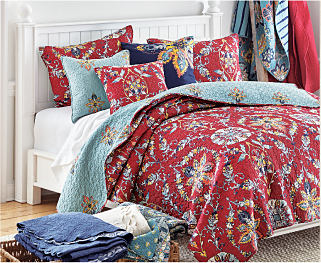 A bed with patterned red bedding and blue accents. Shop bedding.