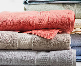 A stack of towels in orange, beige, gray and more colors. Shop towels.