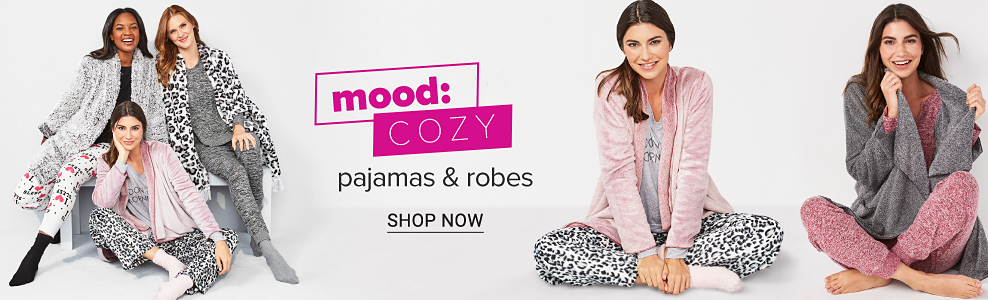 A woman wearing a black & white robe over a black sleep top, multi colored print sleep pants & black socks standing next to a woman wearing a leopard print robe over gray pajamas & gray socks & a woman wearing a pink robe over leopard print pajamas. A woman wearing a gray robe over brick red pajamas. Mood Cozy. Pajamas & robes. Shop now