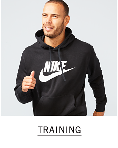 A man wearing a black hoodie with a white Nike logo & swoosh front graphic. Shop training.