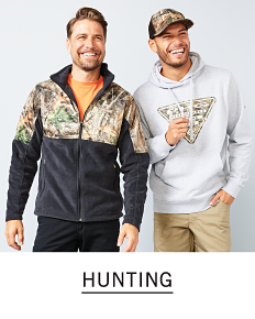 A man wearing a black & camo colorblock fleece & black pants standing next to a man wearing a camo baseball hat, a white hoodie with a front graphic & beige pants. Shop hunting.