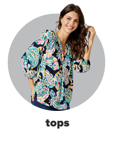 A woman wears a navy blue top featuring a paisley design in bright colors paired with denim pants. Shop tops.
