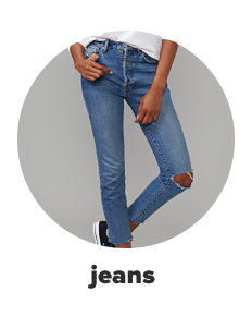 A woman wears distressed blue jeans with a rip in one knee. Shop jeans.