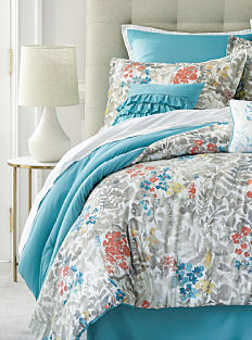 A bed made with a multi-colored floral print comforter & matching pillows. Shop bedroom.