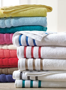 2 stacks of folded bath towels in a variety of colors. Shop bathroom.