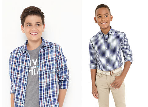 A boy wearing a blue, black & white plaid button front over a gray & white graphic tee standing next to a boy wearing a blue & white check button-front shirt, a white belt & khaki pants. Shirts. Shop now.