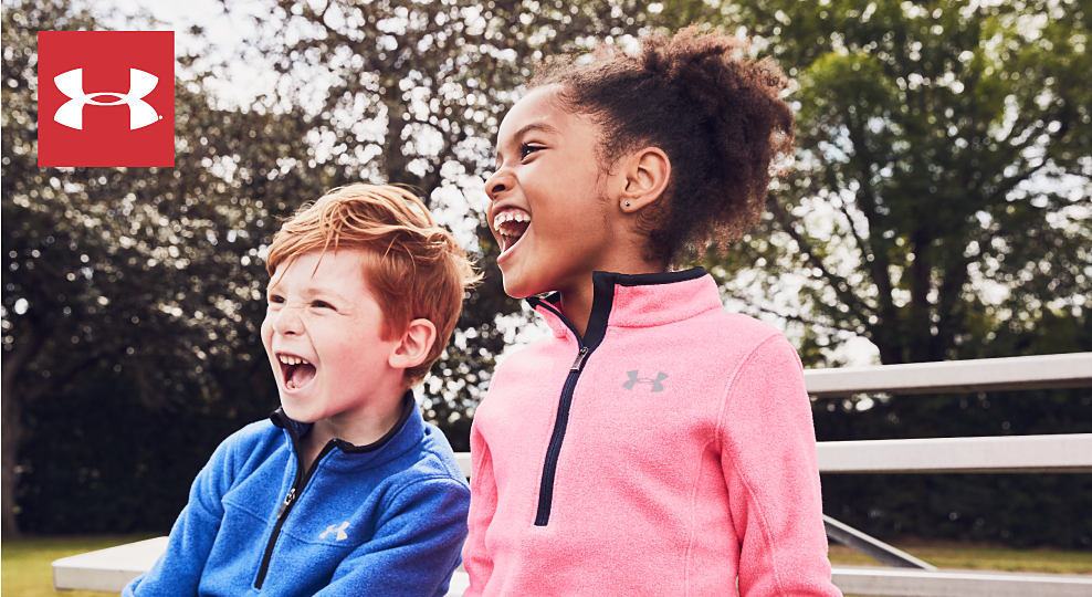 A boy wearing a red, orange & black Under Armour hoodie standing next to a girl wearing a black & pink Under Armour hoodie. Under Armour. Shop girls. Shop boys.
