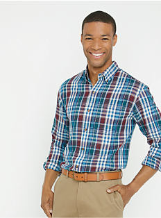 A man wearing a multi-colored plaid button-front shirt and khaki pants. Shop casual shirts.