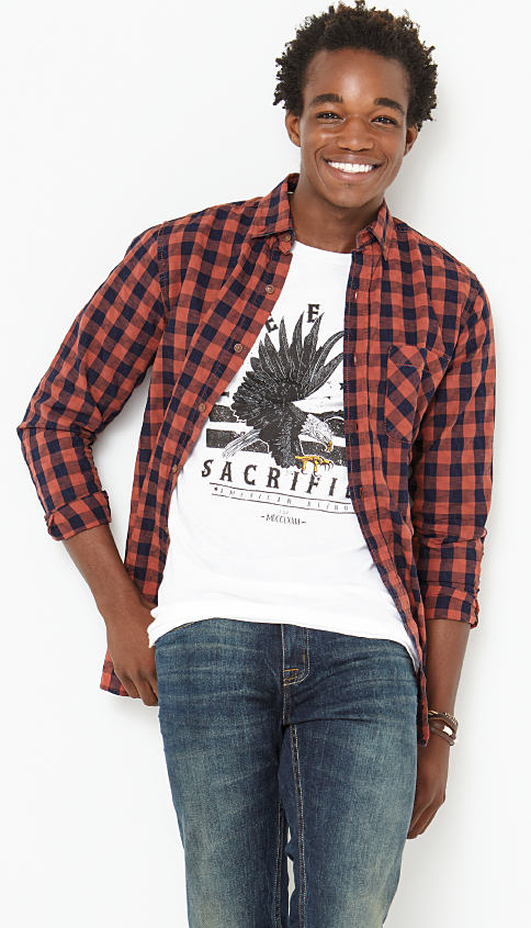 A man wearing a red & black plaid button-front shirt, a black & white graphic tee & blue jeans. Shop True Craft.