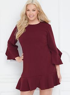 A woman wearing a burgundy velvet dress. Shop dresses.