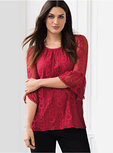 A woman wearing a red long-sleeved peasant blouse & black pants. Shop blouses.