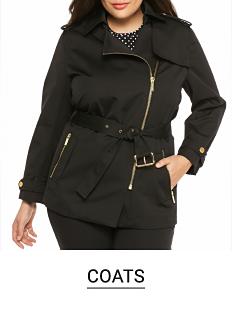 A woman wearing a black side zip coat & black pants. Shop coats.