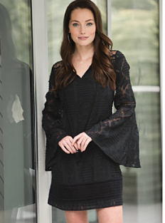 A woman wearing a black dress. Shop dresses.