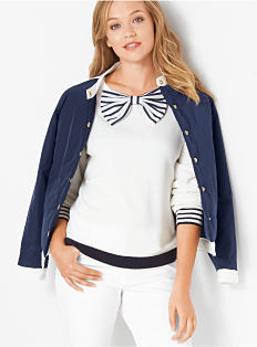 A woman wearing a navy jacket, a white top with blue & white bow neckline detail & white pants. Shop jackets.