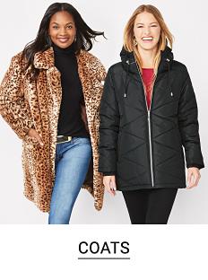 A woman wearing a leopard print coat over a black top & blue jeans standing next to a woman wearing a black winter zip front coat over a red top & black pants. Shop coats.
