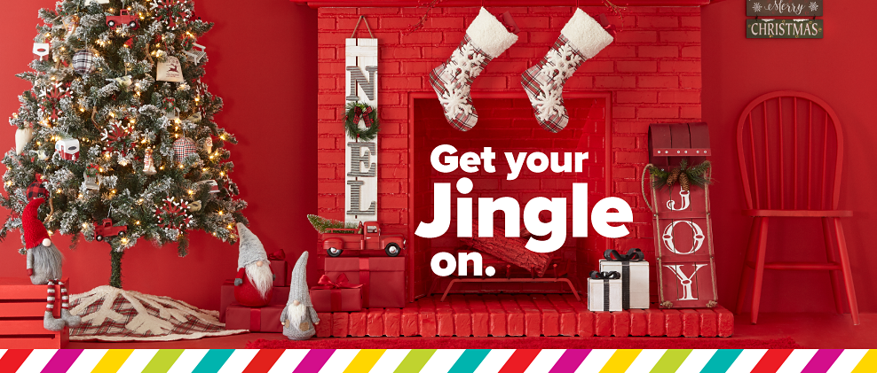 A fully decorated Christmas tree next to a red fireplace surrounded by an assortment of holiday themed decor pieces. Get Your Jingle On.