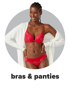 A woman wears a matching red bra and panty set with a white cardigan over top. Shop bras and panties.