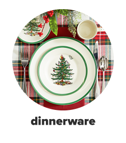 A table setting featuring Christmas-themed dinnerware over a red and green plaid table linen. Shop dinnerware.