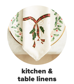 A dinner table set for the holidays featuring a stack of holiday-themed dinnerware including matching dinner plates, salad plates and bowls, a gingham table runner and more. Shop kitchen and table linens.