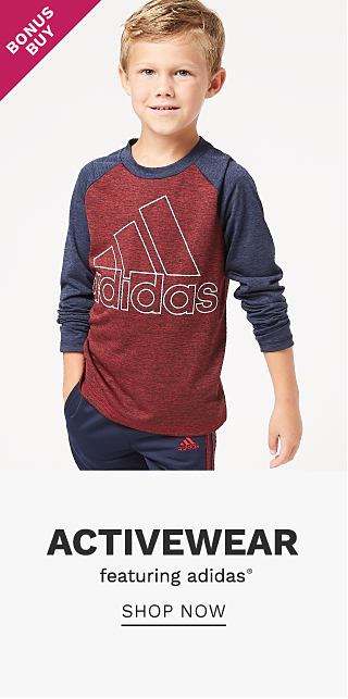 A boy wearing a long sleeved burgundy & white adidas logo shirt with blue sleeves & navy track pants. Bonus Buy. Activewear featuring Adidas. Shop now.