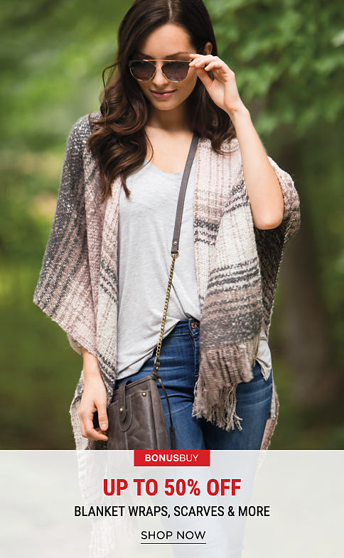 A woman wearing sunglasses, a multi-colored poncho, a white top & blue jeans. Bonus Buy. Up to 50% off accessories.