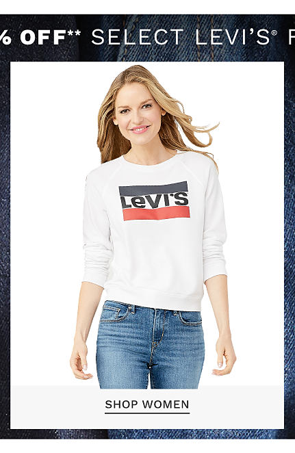 Buy 1, Get 1 50% off select Levi's for the family. Free or discounted items must be of equal or lesser value. A woman wearing a white long sleeved top with a red & black Levi's logo front graphic & blue jeans. Shop women.