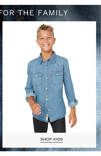Buy 1, Get 1 50% off select Levi's for the family. Free or discounted items must be of equal or lesser value. A boy wearing a blue denim long sleeved button front shirt & blue jeans. Shop kids.