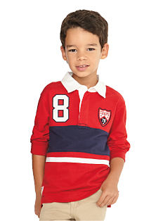 A boy wearing a red, blue & white long-sleeeved soccer shirt & khaki pants. Shop boys 4-7.