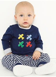 A baby boy wearing a dark blue long-sleeved shirt with a red, blue, green & yellow airplane front graphic, blue & white striped pants & white sneakers. Shop baby boys.